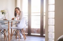 Attractive young happy woman having breakfast at table near window at home — Stock Photo