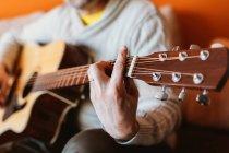 Nahaufnahme eines Mannes, der auf orangefarbenem Hintergrund Gitarre spielt — Stockfoto