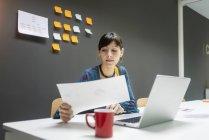 Femme d'affaires travaillant avec des documents tout en étant assis au bureau avec ordinateur portable dans le bureau moderne — Photo de stock