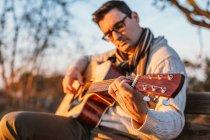 Lässiger Mann mit Brille spielt Gitarre auf Bank im Grünen — Stockfoto