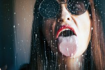 Attractive female with red lipstick licking liquid drops from transparent glass — Stock Photo