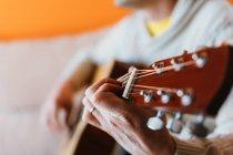 Close-up de homem tocando guitarra no fundo laranja — Fotografia de Stock