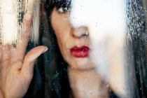 Closeup of sensual female with red lips touching transparent glass — Stock Photo