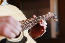 Hände eines Mannes, der auf verschwommenem Hintergrund Gitarre spielt — Stockfoto