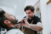 Barbiere con pettine e trimmer taglio barba di maschio seduto in barbiere su sfondo sfocato — Foto stock