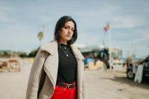 Задумчивая молодая женщина в модном наряде с курткой, стоящей на размытом фоне пляжной парковки и смотрящая в камеру — стоковое фото