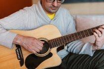 Nahaufnahme eines Mannes, der zu Hause auf dem Sofa Gitarre spielt — Stockfoto
