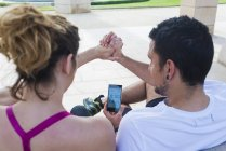 Vista trasera de la pareja en ropa deportiva sentado en el banco, compartiendo el teléfono móvil en el parque - foto de stock