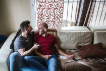 Gay couple relaxing on couch at home — Stock Photo