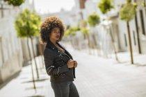 Femme d'Afro-américain attirantavec le cheveu bouclé ajustant la veste en cuir et regardant l'appareil-photo tout en restant sur le fond brouillé de la rue de ville le jour ensoleillé — Photo de stock