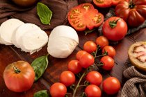 Fresh tomatoes and mozzarella cheese with basil leaves for salad on wooden surface and fabric napkin — Photo de stock
