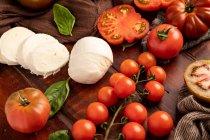 Frische Tomaten und Mozzarella-Käse mit Basilikumblättern für Salat auf Holzoberfläche und Stoffservietten — Stockfoto