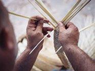 Nahaufnahme Hände von anonymen Handwerker mit Haken für das Weben getrockneter Palmblätter Fasern während der Arbeit in der Werkstatt — Stockfoto