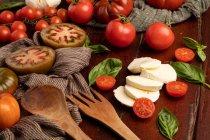 Tomates frescos y queso mozzarella con hojas de albahaca para ensalada en superficie de madera y servilleta de tela - foto de stock
