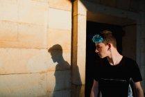 Menino adolescente na moda com franja azul olhando para a sombra na parede de edifício pobre na rua da cidade — Fotografia de Stock