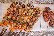 Pinchos de cerdo con verduras y chorizo de barbacoa sobre mantel - foto de stock