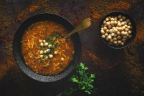 Traditional Harira soup for Ramadan in black bowl on dark tabletop with fresh coriander and chickpeas — Stock Photo