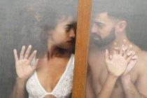 Красивый латиноамериканец, соприкасающийся лицом к лицу с соблазнительной афроамериканкой в кружевном лифчике, стоя за мокрым окном дома — стоковое фото