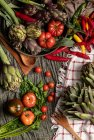 Set of various fresh vegetables and cloth napkins rustic on table in kitchen — Stock Photo