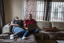Cheerful gay couple using laptop while relaxing on couch — Stock Photo