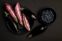 Свежие спелые баклажаны и черника в миске на черном столе — стоковое фото