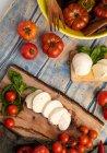 Tomates frescos y queso mozzarella con hojas de albahaca para ensalada sobre tabla de madera y tela - foto de stock