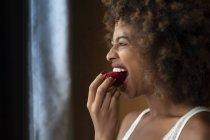Mulher afro-americana sedutora com cabelo encaracolado comendo morango maduro em casa — Fotografia de Stock