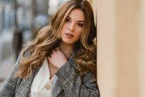 Портрет молодой привлекательной женщины, опирающейся на стену на улице — стоковое фото