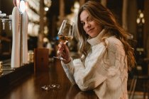 Attraente giovane signora in maglia alla moda maglione godendo di vino bianco mentre seduto al bancone in pub alla moda — Foto stock