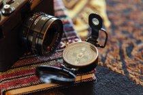 Nahaufnahme einer arrangierten Vintage-Fotokamera mit Kompass auf rustikalem Notizblock — Stockfoto