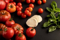 Ripe red tomatoes and basil leaves for salad on black background near slices of fresh mozzarella cheese — Stock Photo
