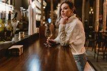 Elegante donna premurosa bere vino al bancone nel bar — Foto stock