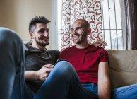Feliz pareja gay relajándose en el sofá en casa - foto de stock