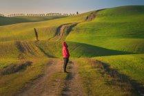 Pessoa de jaqueta em pé na estrada rural vazia em majestosos campos verdes da Itália — Fotografia de Stock