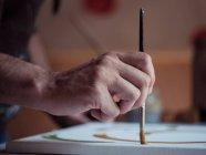 Рука анонимного художника с кистью и рисунком зеленой краской на холсте в студии — стоковое фото