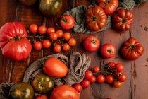 Pomodori freschi assortiti e tovaglioli in tessuto sul tavolo di legname in cucina — Foto stock