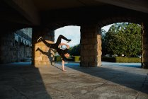 Teenager break dancing in arch in sunlight — Stock Photo
