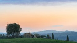 Paysage pittoresque de champs verts avec chalet et arbres au coucher du soleil, Italie — Photo de stock
