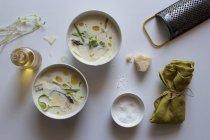 Tazones de deliciosa sopa de crema de espárragos con queso y hierbas sobre fondo blanco - foto de stock