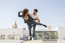 Multiracial hombre y mujer riendo y equilibrando en la pared mientras se divierten en la calle de la ciudad durante la fecha - foto de stock