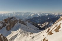 Vue panoramique de la pente enneigée sur l'arrière-plan des montagnes dans la brume et la lumière du soleil, Suisse — Photo de stock