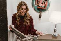 Stylish woman reading magazine and smiling — Stock Photo