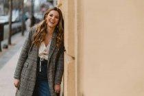 Senhora bonita no casaco da moda rindo e olhando para a câmera enquanto se inclina na parede do edifício no fundo borrado da rua da cidade — Fotografia de Stock