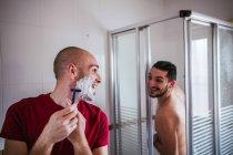 Гей-пара веселится в ванной вместе — стоковое фото