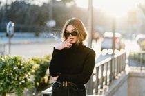 Mulher elegante fumar cigarro perto da estação de metro na rua ensolarada — Fotografia de Stock