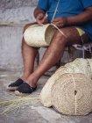 Anonyme Kunsthandwerker weben schönen Korb mit geflochtenen getrockneten Palmfasern — Stockfoto