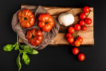 Fresh ripe tomatoes, mozzarella and basil leaves on piece of wood on black background — Stock Photo