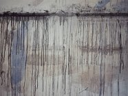 Spills of dark paint on surface of weathered cement wall in artist workshop — Stock Photo