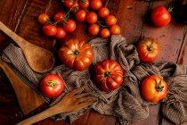 Pomodori freschi assortiti e tovagliolo di tessuto su tavolo di legname in cucina — Foto stock