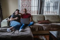 Happy gay couple relaxing on couch and using smartphone and laptop — Stock Photo